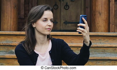 Pretty young girl smiling to take a selfie on mobile