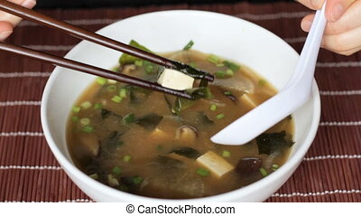 Close up of miso soup eaten with chopsticks and white spoon...