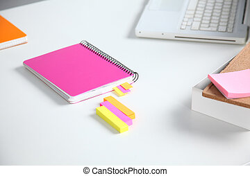 Closeup of white desktop with notepads, pen, coffee cup and...