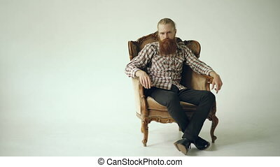 Bearded man sitting luxury armchair and looking into camera...