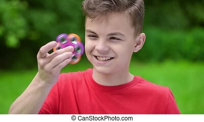 Teen boy with spinner in park - Child having fun outdoors...