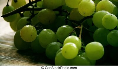 Green grapes on a wooden table. 4K close-up shot