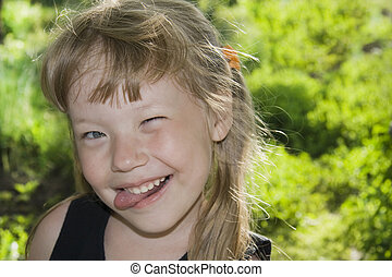 Little girl sticking out tongue. - Little girl grimaces and...