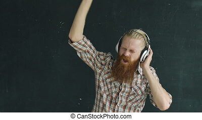 Slowmotion of bearded young man in headphones dancing while listen to music on black background