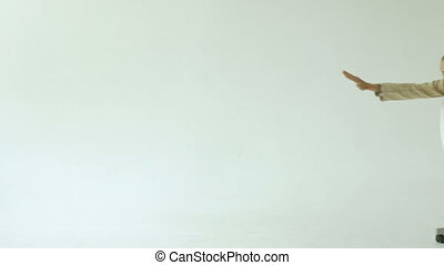 Slowmotion of Bearded funny businessman have fun riding on office chair on white background