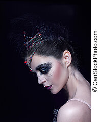 Portrait of the ballerina in the role of a black swan on...