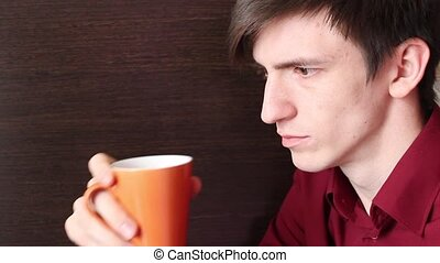 A young guy drinking from an orange mug, always looking away...