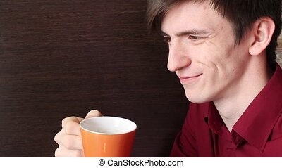 A young guy smiles, takes a slow sip from an orange mug -...