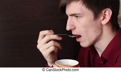 A young guy licks a teaspoon with his mouth and puts it in...
