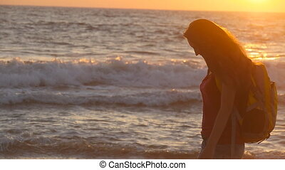 Young female tourist with backpack walking along sea beach at sunset. Beautiful young traveler woman going on ocean shore at sunrise. Girl hiker stepping during travel or summer vacation. Slow motion