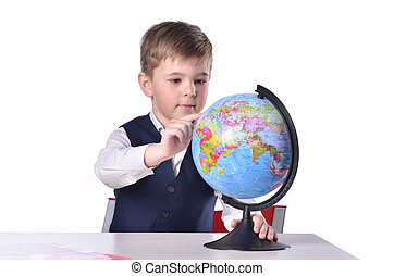 Schoolboy at the desk searching something on a globe of...