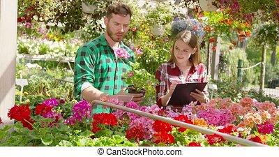 Gardeners doing paperwork - Male gardener standing with...