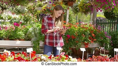 Gardener using tablet - Smiling young female botanist using...