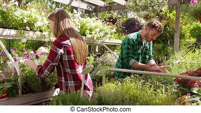 Man and woman in garden - Young professional male and female...