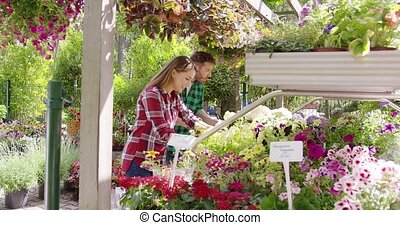 Gardeners working with flowers - Side view of male and...
