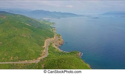 Aerial View Highway among Hills and Ocean against Mountains...