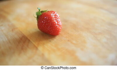 One strawberry berry lies on a wooden board that rotates...