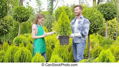 Gardeners with potted tree - Horizontal outdoors shot of man...
