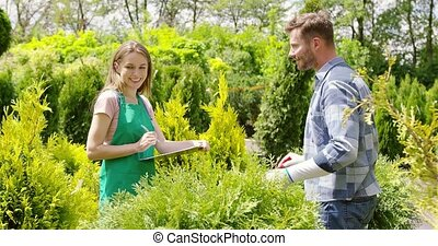 Gardeners working with papers - Young gardener woman...