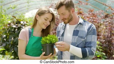 Man smelling potted plant - Horizontal indoors shot of woman...