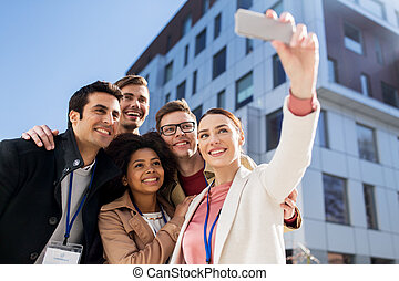 happy people with conference badges taking selfie -...