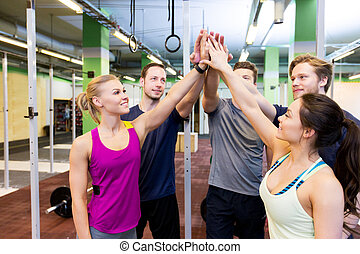 group of happy friends making high five in gym - fitness,...