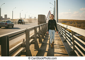 girl goes on road bridge. lonely young woman in black Leather jacket autumn, walking over the bridge which goes transport.