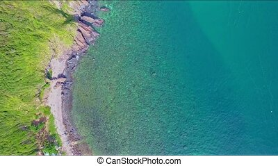 Aerial View Motion over Steep Cliff Coast with Green Slopes...