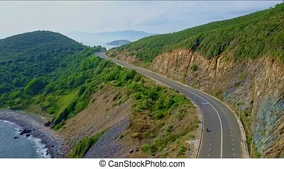 Aerial View Highway on Steep Rocky Slopes above Ocean -...
