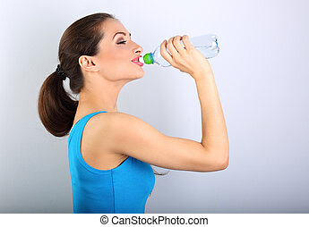 Beautiful happy sporty slim woman holding and drinking water...