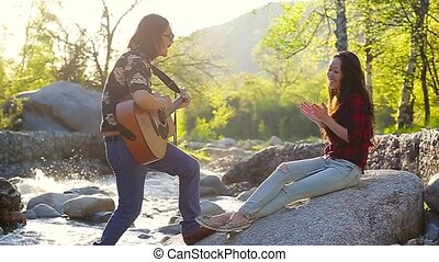 Young romantic couple enjoying time outdoors. Man is singing...