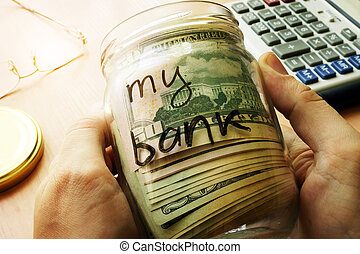 Home finances and savings concept. - Jar with dollars and...