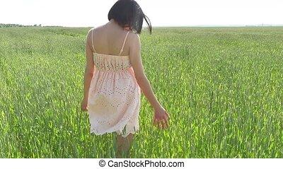 Girl field wheat. Beautiful girl walking on a green field...