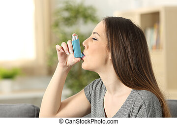 Asthmatic woman using an inhaler - Side view of an asthmatic...