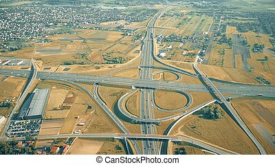 Aerial shot of modern highway interchange in outskirts on an autumn sunny day