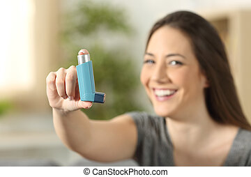 Girl showing an asthma inhaler sitting on a couch in the...