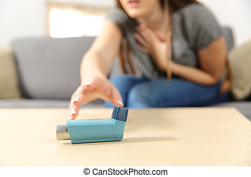 Girl suffering asthma attack reaching inhaler sitting on a...