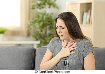 Woman suffering respiration problems sitting on a couch in...
