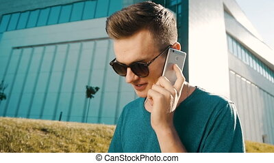 Young Man Talking Phone - Young attractive man wearing blue...