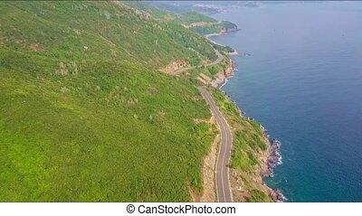 Drone Flies above Highway Running between Hills and Ocean -...