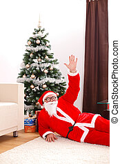 Santa claus laying on floor in front of christmas tree