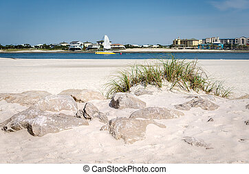 White sand beach with rocks and grass
