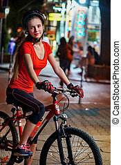 City night bicycle ride. Girls wearing bicycle helmet....