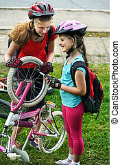 Bicycle tire pumping by child bicyclist. Girl repair bicycle on road .