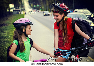 Bicyclist child ride on city bicycle path . Girls wearing...