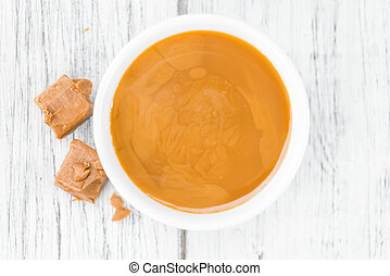 Portion of Caramel Sauce on wooden background (selective...