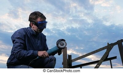 A young man polishes a metal angle grinder at sunset....