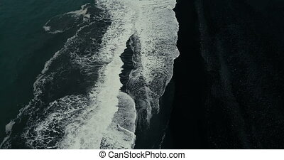 Aeial view of the wave coming on the shore of the black...