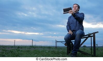 A young man is sitting and talking on the tablet at sunset. A field of green grass behind. Beautiful sky.
