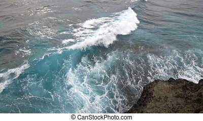 Sea waves explode on the rocky shore